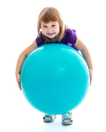 Little girl having fun raises a large sports ball. Happy childhood, fashion, autumnal mood concept. Isolated on white background photo