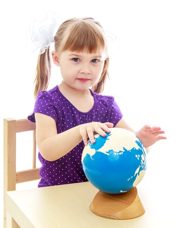 long hair boy: very clever little girl sitting at a table in the Montessori classroom. Stock Photo