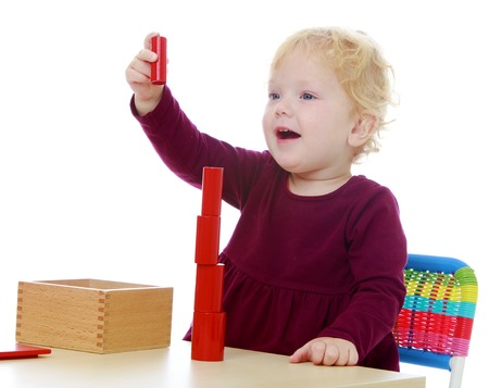 montessori: Little girl collects a pyramid of red details in a comma Montessori school.White background, isolated photo. Stock Photo