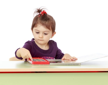 montessori: Little girl sitting at a table and read e-books. Montessori Wednesday.White background, isolated photo.