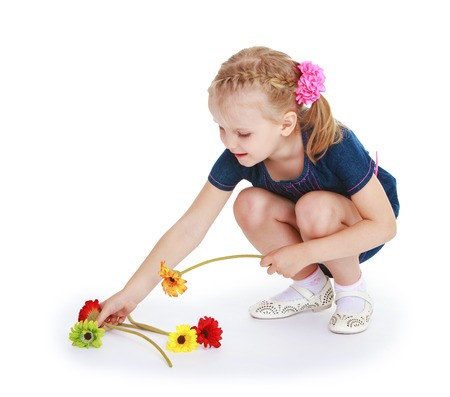 Little girl collects the scattered flowers .White background, isolated photo. photo