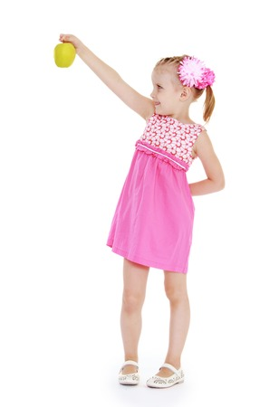 The girl in a pink dress holding at arms length green apple.White background, isolated photo. photo