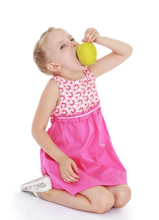 Girl eats a big green apple.White background, isolated photo. photo