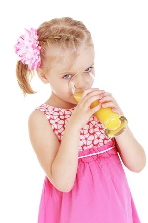 Girl drinking orange juice from a large glass.White background, isolated photo.