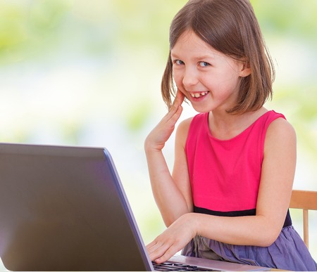 baby 4 5 years: Little girl laughs looking at laptop screen.