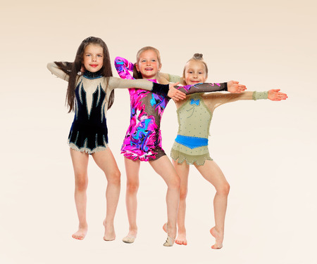 baby 4 5 years: three gymnasts of the girl of 6 years carry out exercises.isolated on white.