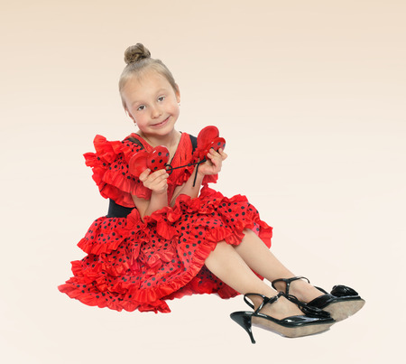 baby 4 5 years: little girl in a bright red dress sitting on the floor in shoes on a high heel.the concept of fashion.