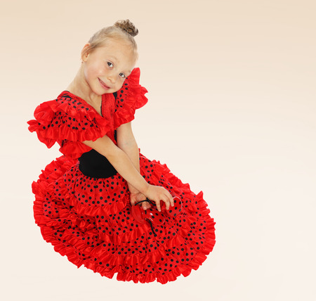 baby 4 5 years: Very sweet little girl sitting on the floor in a bright red dress.the concept of fashion.