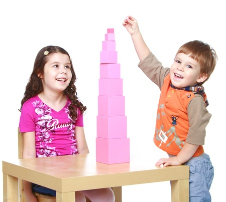Smiling brother and sister playing together building pink tower, which stands on the table.Isolated on white background portrait.