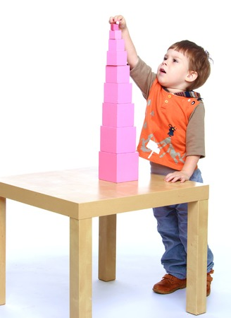 baby 4 5 years: Boy builds pink tower in Montessori school.Isolated on white background portrait.