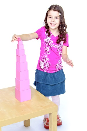 baby 4 5 years: pink girl builds a tower in the school of Maria Montessori.Isolated on white background portrait.