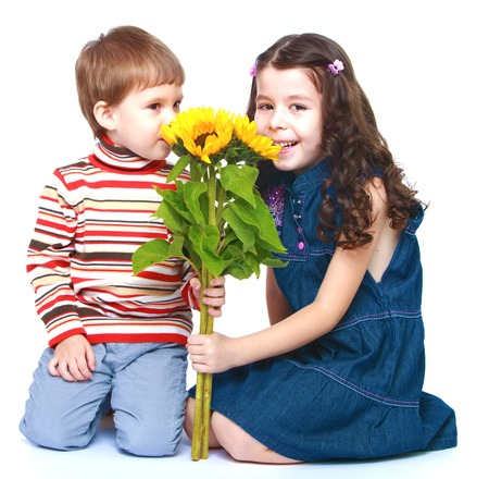 baby 4 5 years: Brother and sister sniffing bouquet of yellow flowers.Isolated on white background portrait.
