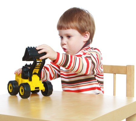 baby 4 5 years: little boy playing with a toy tractor sitting at the table.Isolated on white background portrait.