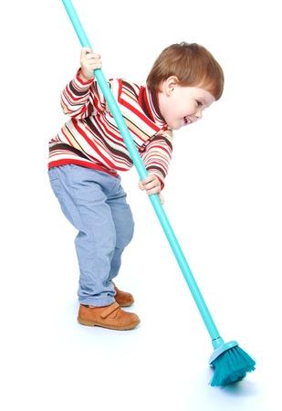 Jongetje vegen de vloer met een brush.Isolated op witte achtergrond portret.