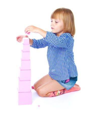 charmant klein meisje verzamelt in de Montessori klas piramide geïsoleerd op een wit paard