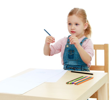 montessori: Little girl draws pencils sitting at the table.Childhood education development in the Montessori school concept. Isolated on white background.
