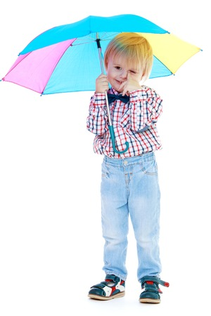 montessori: Little boy stands under a colorful umbrella.Childhood education development in the Montessori school concept. Isolated on white background.