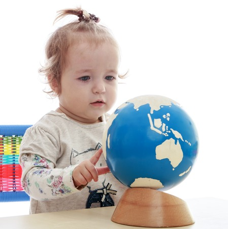 Pretty little girl spinning globe.Isolated op een witte achtergrond.