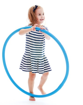 beach wrap: Little girl in a striped dress is holding a hoop.Isolated on white background.