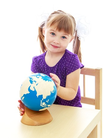 little table: Charming little girl sitting at the table does not consider the globe. Stock Photo