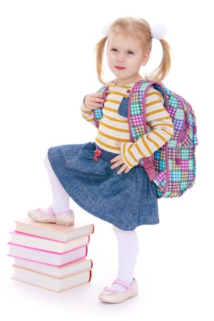 classbook: Adorable little girl put her foot on a stack of books.Isolated on white background. Stock Photo