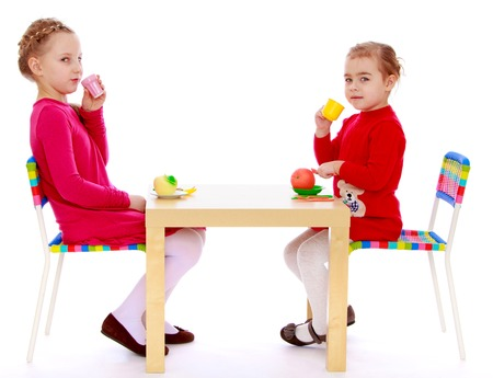 Two girls sitting at the table and drink tea.Isolated on white background. photo