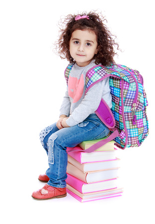 classbook: Little girl sitting on a pile of books.Isolated on white background.