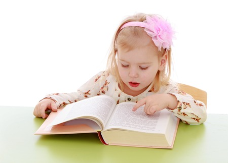 Little girl reading a book with enthusiasm.Isolated on white background. photo
