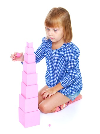 Meisje, zittend op zijn schoot bouwt hoge roze toren, Montessori school.Isolated op een witte achtergrond.