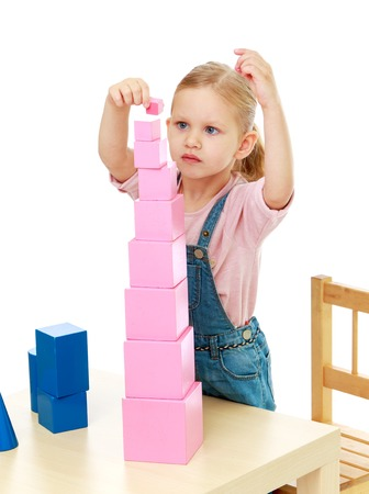 montessori: Little girl collects a large pink pyramid. Montessori School.Isolated on white background.