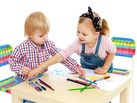 Jongen en meisje tekening met potloden zit aan de table.Isolated op een witte achtergrond. Stockfoto