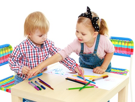Boy and girl drawing with pencils sitting at the table.Isolated on white background.