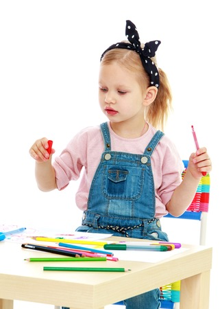 Little girl draws pencils sitting at the table.Isolated on white background. photo