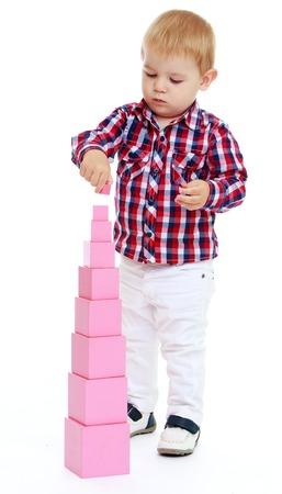 little boy builds Red Pyramid, Montessori KindergartenIsolated on white background. Archivio Fotografico