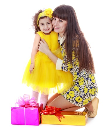 charming mother and daughter beside gifts.Isolated on white background. photo