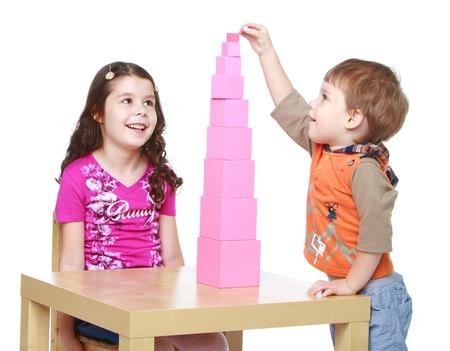 Broer en zus verzamelt Rode Piramide in de Montessori kindergarten.Isolated op een witte achtergrond, Lotus Childrens Center.