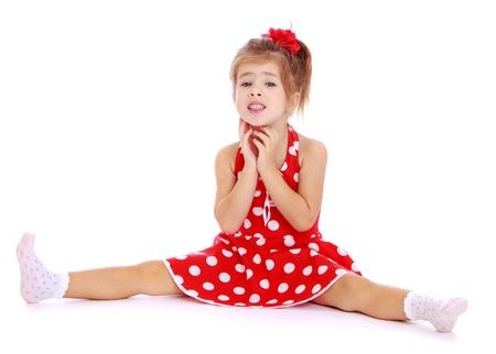 legs spread: Bella bambina seduta a gambe aperte wide.Isolated su sfondo bianco, Lotus Childrens Center.