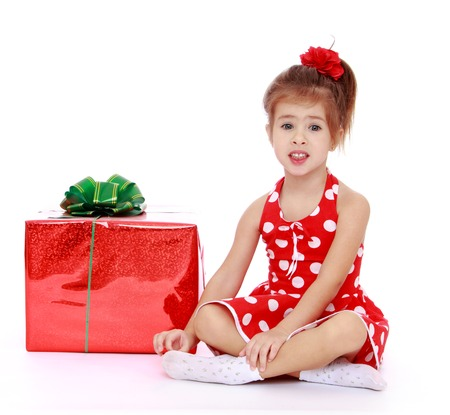beautifully wrapped: Adorable little girl sitting on the floor folding legs in Turkish, next to her is a big red beautifully wrapped gift.Isolated on white background, Lotus Childrens Center.