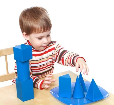 Weinig jongen speelt kubussen en kegels zitten aan de tafel, Montessori kindergarten.Isolated op een witte achtergrond, Lotus Childrens Center.
