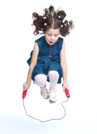 Cheerful little girl jumping on a skipping rope.Isolated on white background, Lotus Childrens Center. Archivio Fotografico