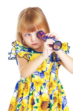 enthusiastic little girl looking into a kaleidoscope.Isolated on white background, Lotus Childrens Center.