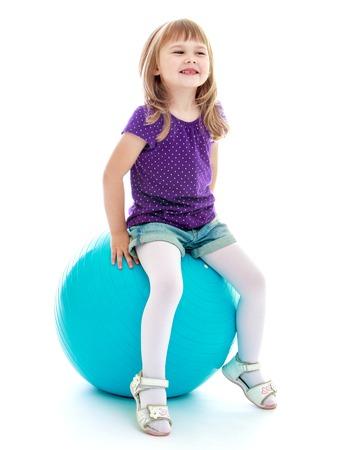 Klein meisje in korte broek zitten op de grote blauwe linen.Isolated op wit.