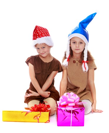 beautifully wrapped: Happy childhood, the family concept.Two girls in caps of Santa Claus sitting in front of beautifully wrapped gifts. Isolated on white.