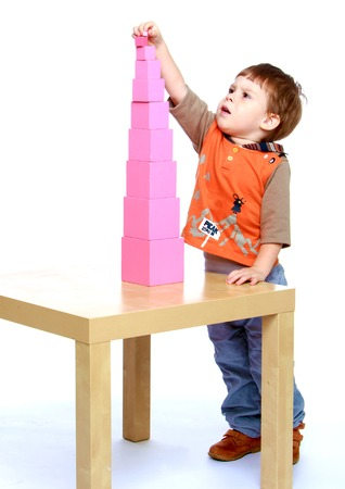montessori: Serious little boy collects Red Pyramid in the Montessori school.Isolated on white.