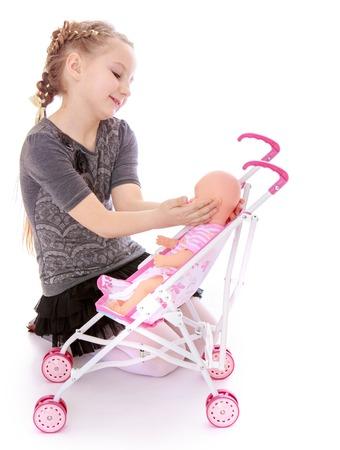 Mooi meisje zet haar pop in een stroller.Isolated op wit.
