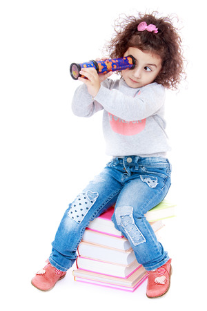 romantic little girl with curly hair sitting on a pile of books and smotrmt a kaleidoscope.Isolated on white. Imagens