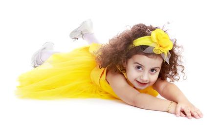 barrettes: Stylish bambina in un abito giallo e mollette nei capelli curly.Isolated su bianco.