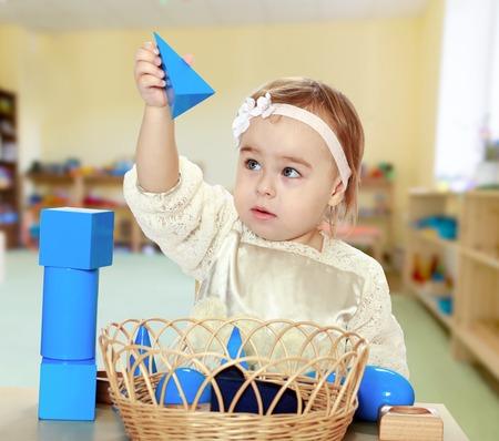 pretty little girl puts cubes Montessori classroom.