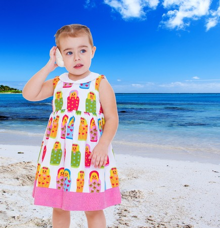 posted: Thoughtful little girl posted a shell to your ear while standing on the beach. Stock Photo