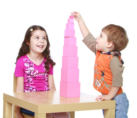 montessori: brother and sister building a Red Pyramid, Montessori school. Isolated on white. Stock Photo
